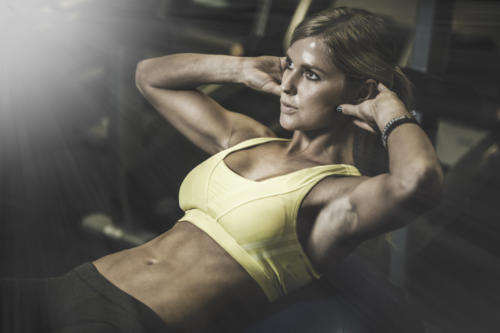 Young fit woman excecising ingym